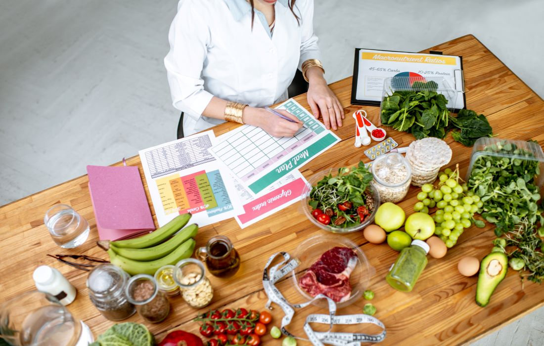 woman making meal plan with healthy food on table