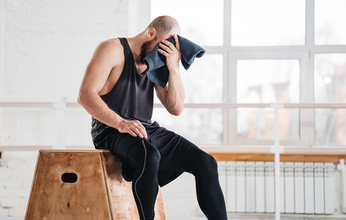athlete in gym wiping sweat off forehead