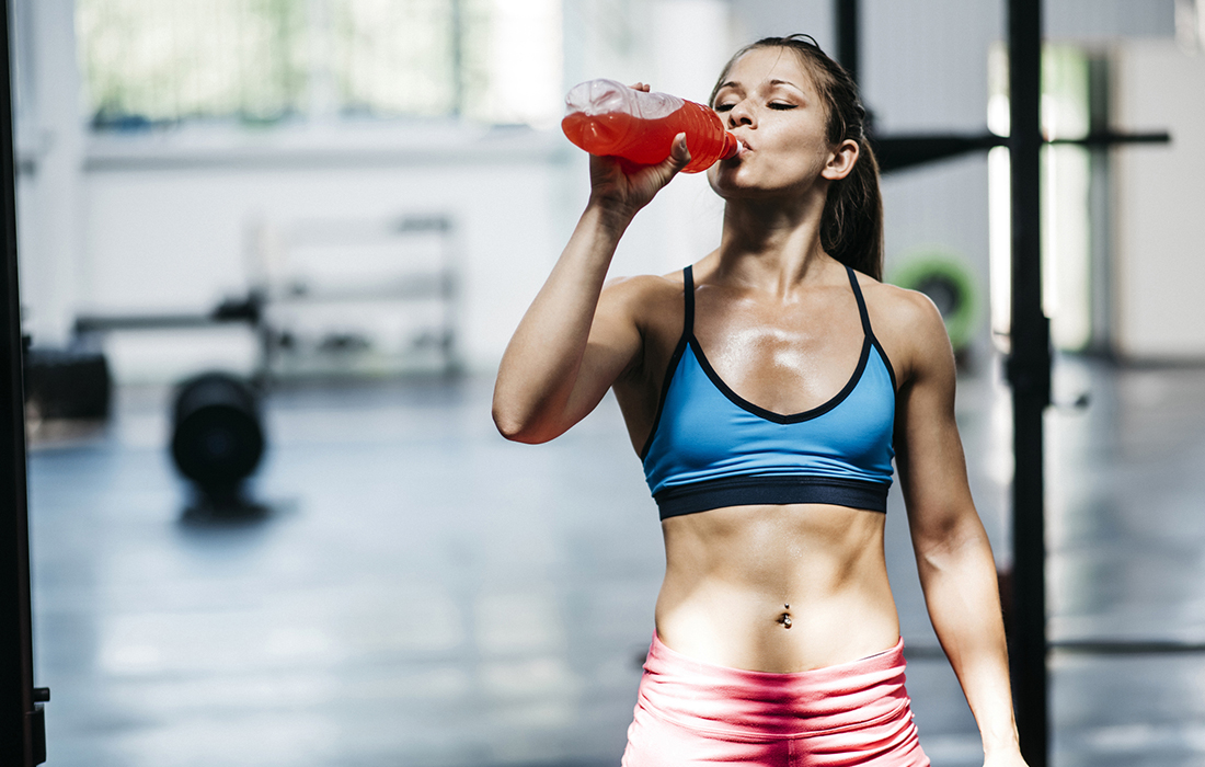 woman in the gym drinking coloured fluids electrolytes