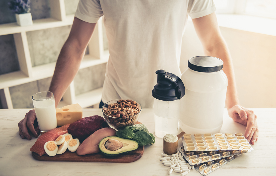 man in kitchen cooking balanced meal protein