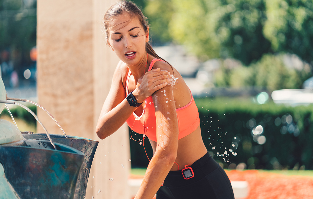 dehydrated runner splashing water on herself