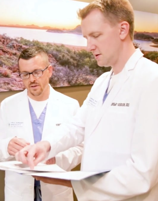 Dr. Goodson and Dr. Bryan looking at a patient information folder