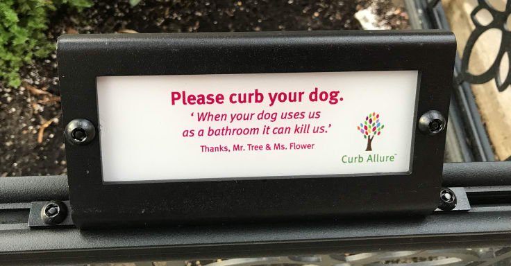 """A sign that says """"Please curb your dog. When dogs us as a bathroom it kills us."""""""