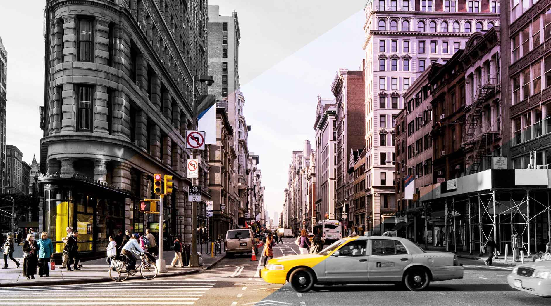 A predominately black and white image of a busy city street in New York City; a diagonal stripe through the middle reveals the image's color, including the yellow a taxi