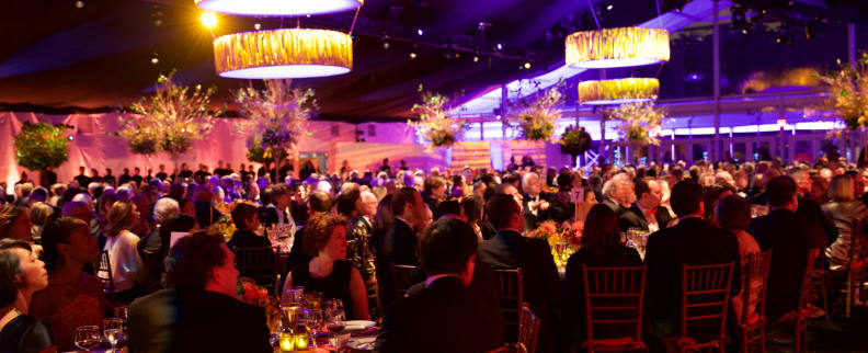 People sitting at round tables for a gala event