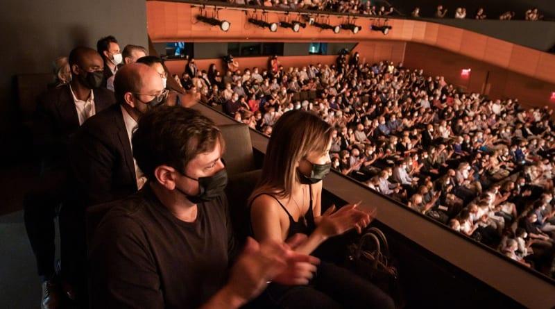 Audience members smile in their seats