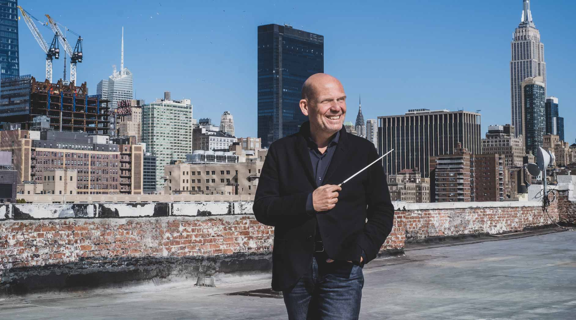 Music Director Jaap van Zweden holds a baton in front of a cityscape.