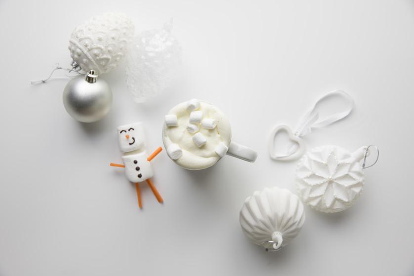 Kopp med julemelk omkranset av juledekorasjoner