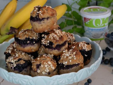 Muffins med blåbær og banan stablet som en pyramide på et fat. I bakgrunnen er en klase gule bananer, en skål med blåbær og et beger Q drømmelett