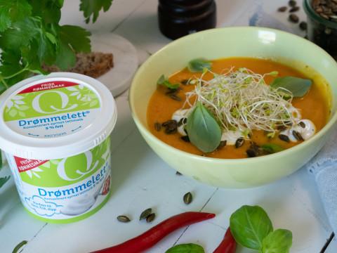 Suppeskål med gulrot- og søtpotetsuppe toppet med ristede kjerner og alfalfaspirer. En boks med Q drømmelett, og to røde chili og en kvast urter ligger på bordet
