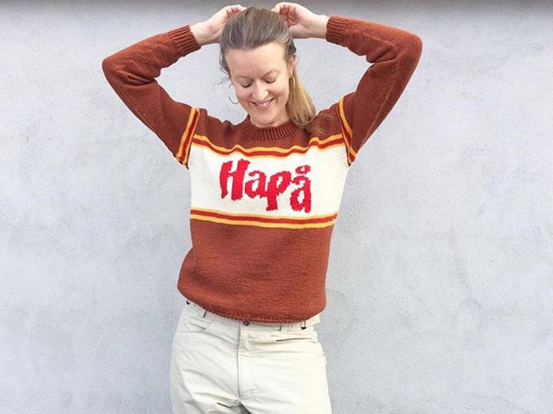 Flerfarget strikkegenser i brunt, hvitt og rødt med HaPå-logo