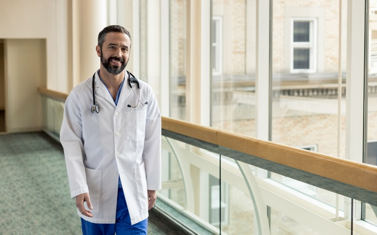 OAG physician smiling while walking down hospital hall