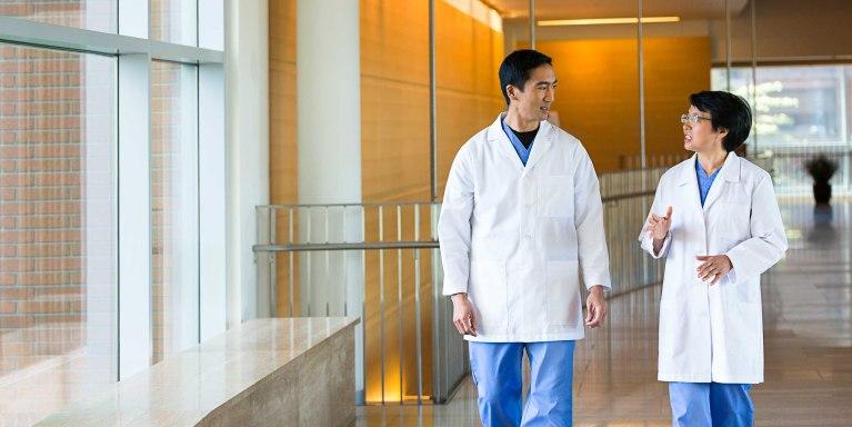 oag-careers-hero-two-doctors-talking-and-walking-down-hall