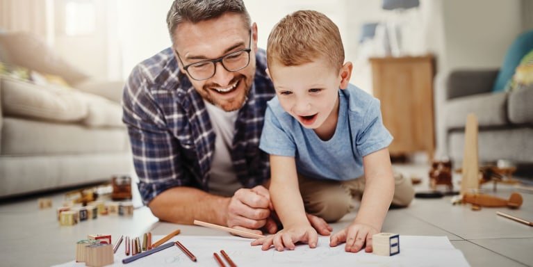 Happy father and son drawing on the floor