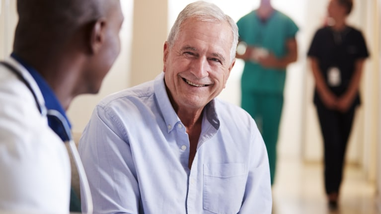 Doctor and elderly patient talking and smiling