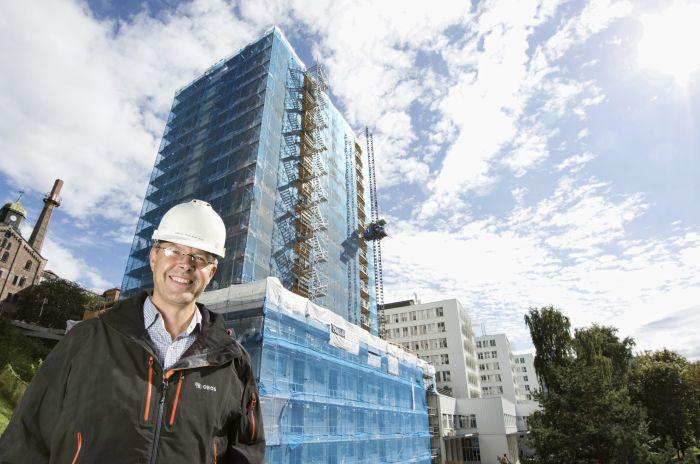Mann med hjelm foran en høy bygning