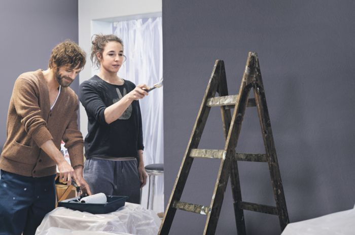 Et par som maler veggene i leiligheten
