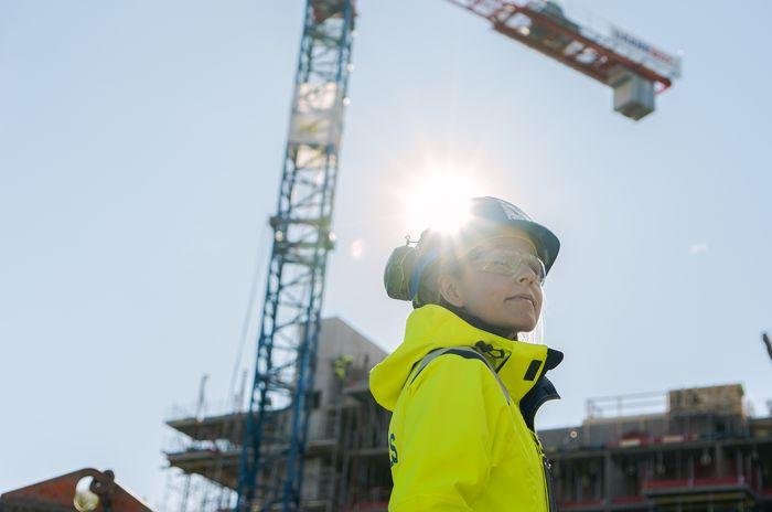 Bilde av en kvinne med hjelm og vernebriller på en byggeplass