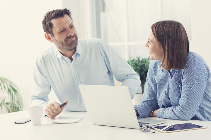 Bildet viser to personer foran et skrivebord med PC.