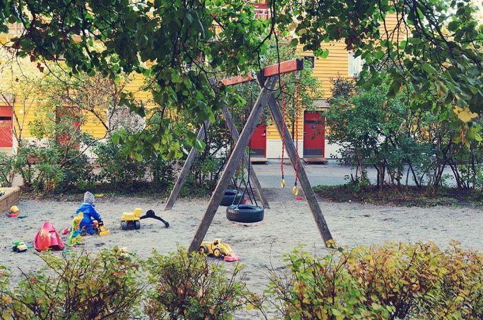 Et barn leker i sandkassa med masse leker rundt seg.