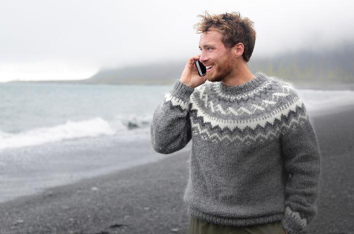 mann-i-ullgenser-på-strand-snakker-i-mobil