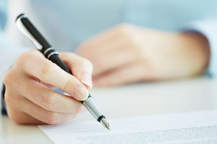 Hånd som skriver med penn på papir