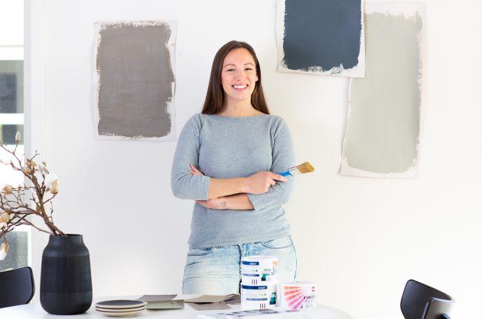 Ung kvinne foran en vegg med malingsprøver.