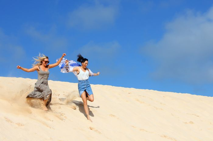 To kvinner løper ned en sanddyne