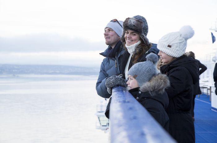 En vinterkledd familie på dekk