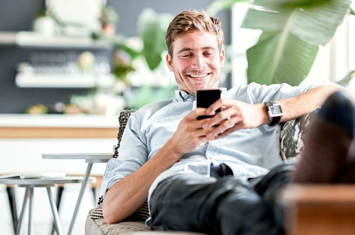 Mann sitter i sofaen og ser på mobilen