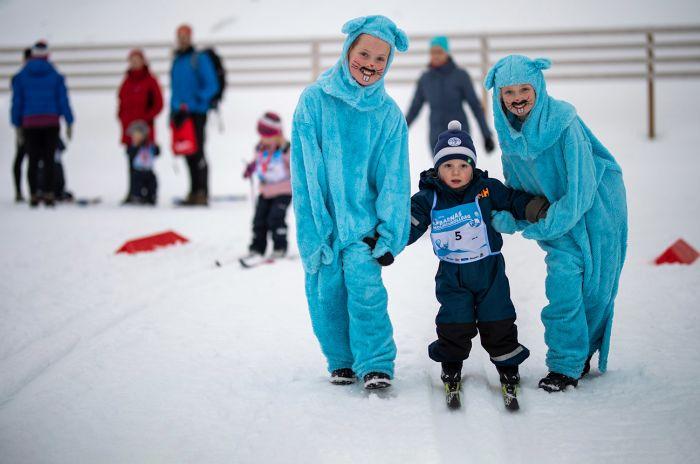 To utkledde harer som hjelper et barn på ski
