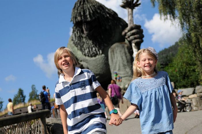 Gutt og jente hånd i hånd foran troll-skulptur