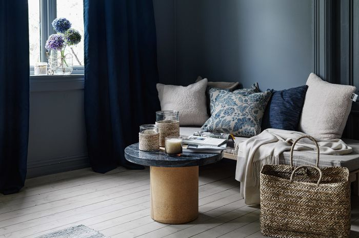 Stue med blå velurgardiner, sofa og sofabord, lyst tregulv og mørkeblå vegger
