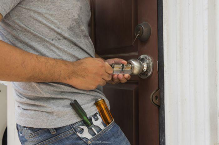 En låsesmed jobber med å reparere en dør som har gått i vranglås.