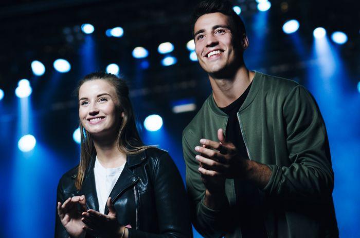 To ungdommer, en gutt og en jente, klapper og smiler på konsert.