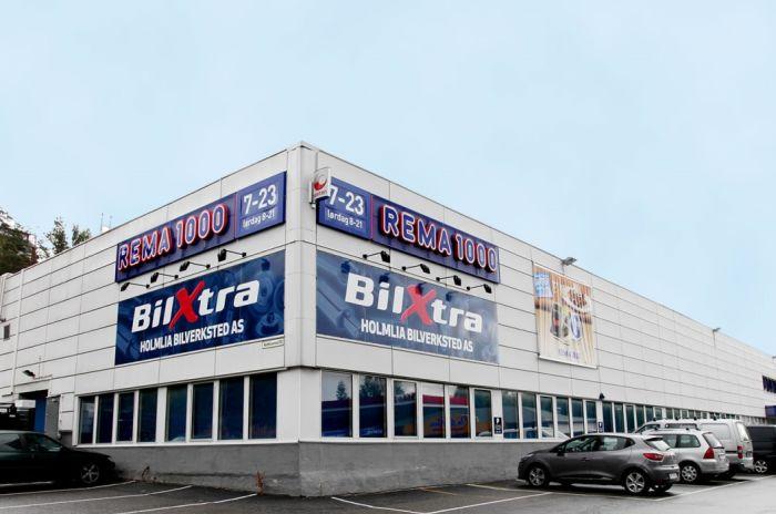 Bilde av Holmliaveien 100. Næringsbygg i hvit bølgeblikk med parkeringsplass utenfor.