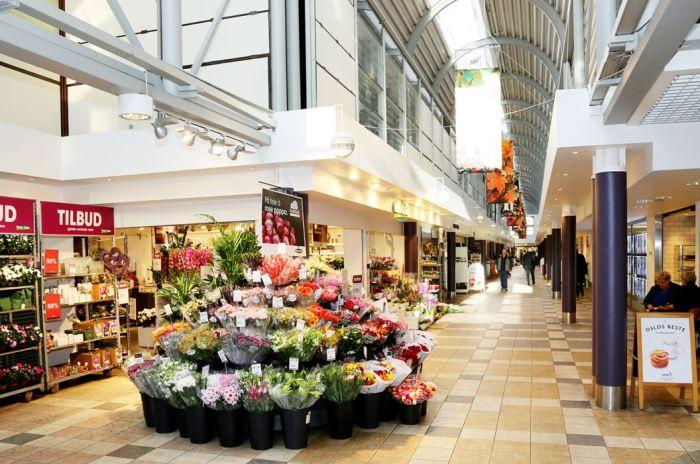 Bilde av Sandaker senter innendørs, med en blomsterbutikk i fokus.