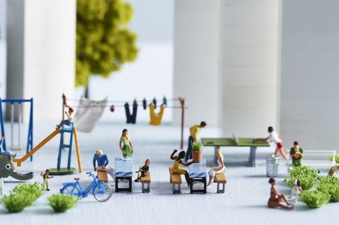 Miniatyrmodeller som illustrerer en bakgård med forskjellige mennesker og aktiviteter