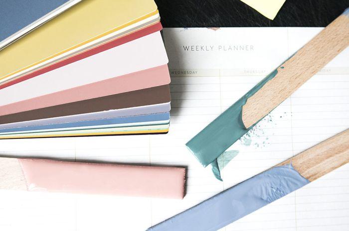 Papper med olika kulörprover och tre pinnar med tre olika färger på