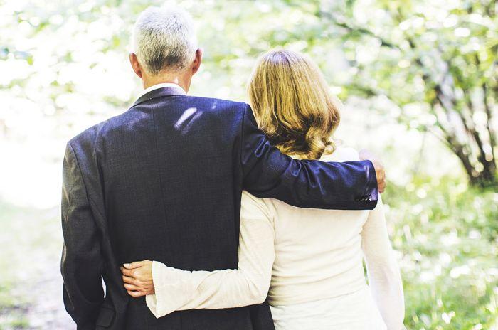 En mann og en dame med ryggen til holder trøstende rundt hverandre.
