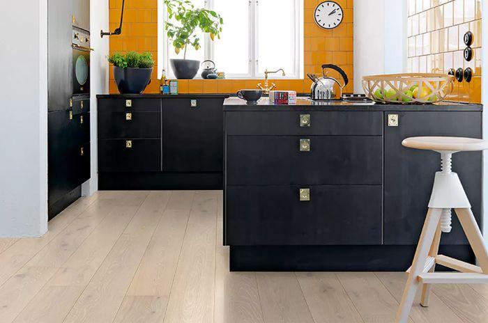 Et kjøkken med svart innredning og gulv med lys parkett.