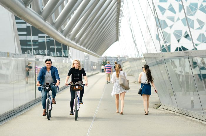 Bysykkelsyklister og gående over en gangbro ved barcode, Oslo. Fotograf Holien Mo