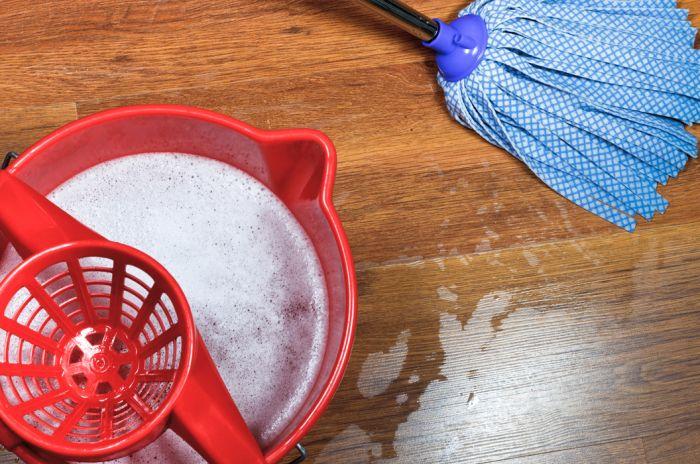 En rød vaskebøtte med såpevann og en blå mopp på et tregulv