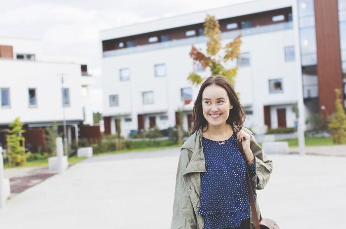 En smilende, ung kvinne er ute og går med bygninger i bakgrunnen