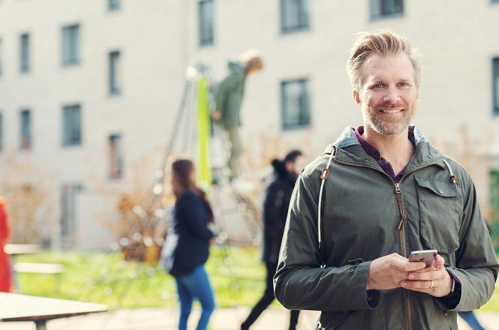 En mann smiler og folk leker og rusler bak ham i et nabolag