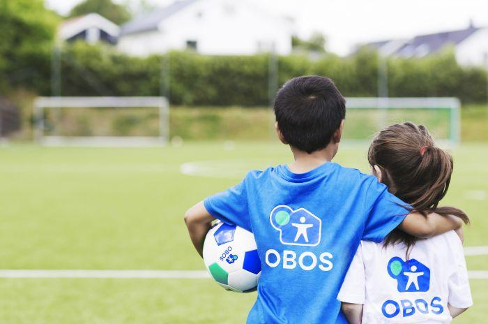 To barn i OBOS-tskjorter som ser mot et fotballmål