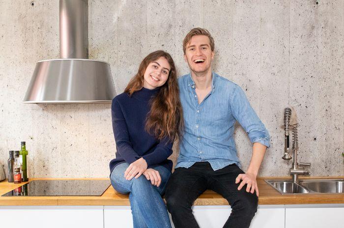 Et smilende par sitter på kjøkkenbenken hjemme hos seg selv.