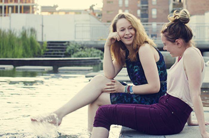 To venninner sitter ved et vannspeil i Kværnerbyen