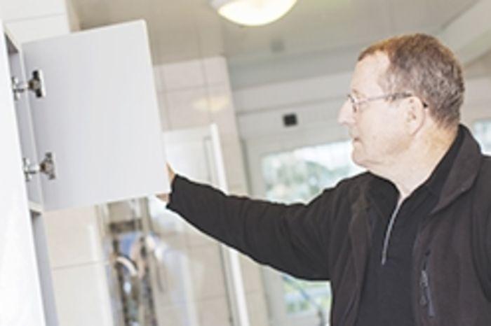 Bilde av mann som sjekker tingenes tilstand i et skap