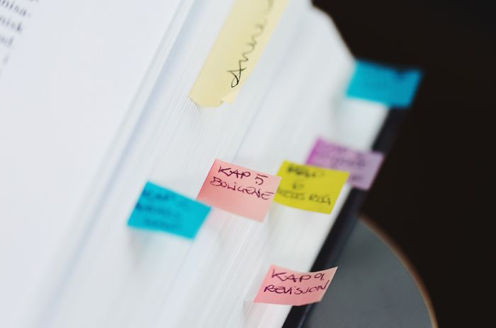 Utsnitt av en lovbok der noen av sidene er markert med små postilapper